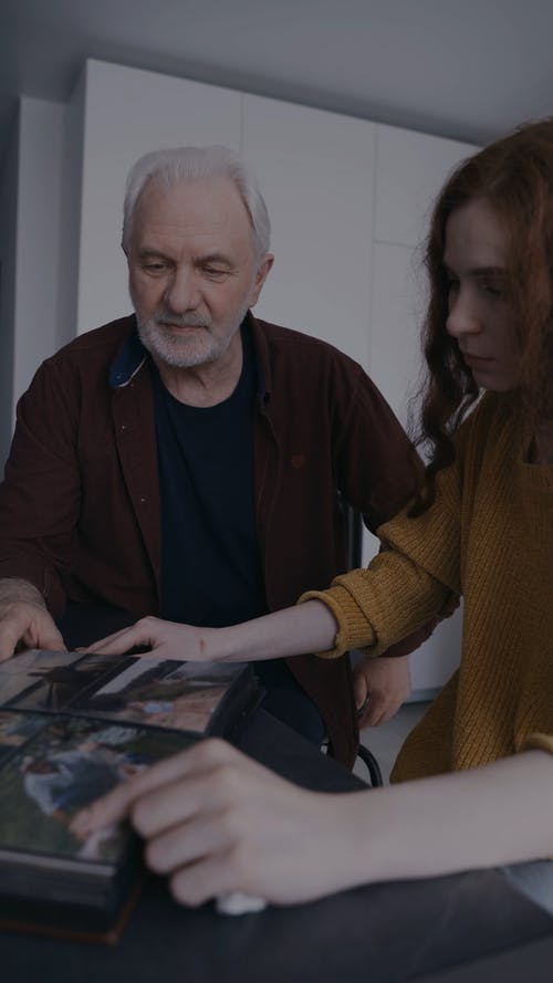 Elderly Man and Woman Looking at Pictures in a Photo Album