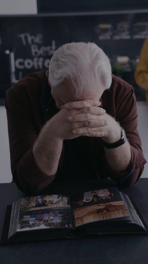 An Elderly Man Looking at a Photo Album
