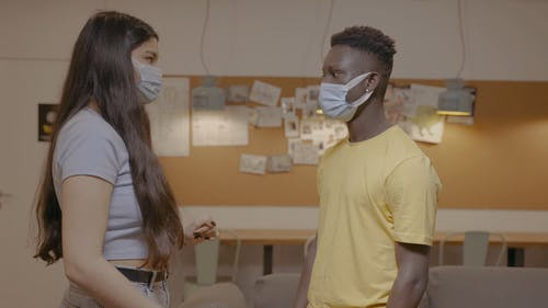Man and Woman Talking while Removing Facemask