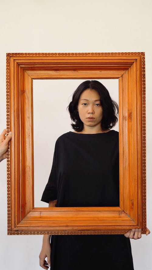 A Woman Holding Flowers and a Picture Frame