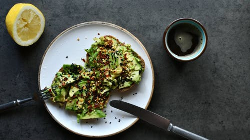 A Person Eating Avocado Toasts and Drinking Coffee