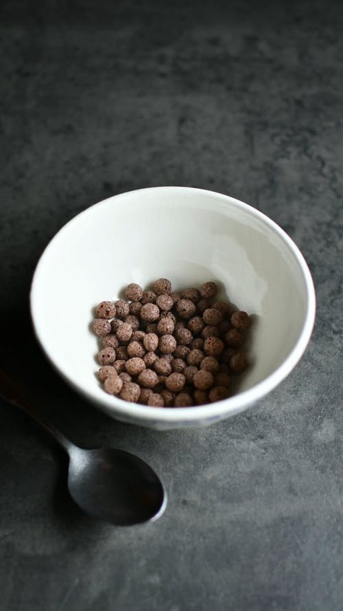 A Person Putting Chocolate Cereals with Milk in a Bowl