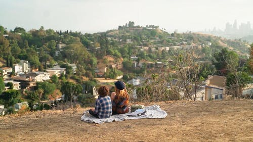 People Talking While Sitting on a Picnic Blanket