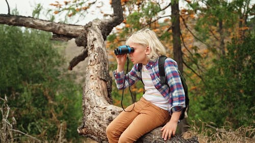 A Girl Looking at the View using a Binocular