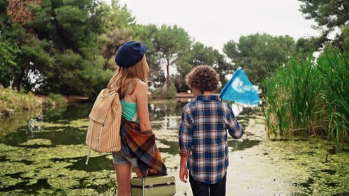 Back View Footage of Children Standing Near a Pond