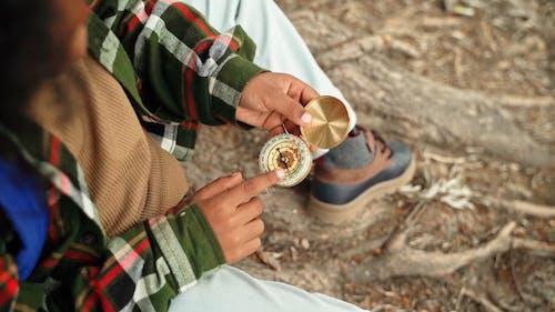 A Boy Holding a Compass