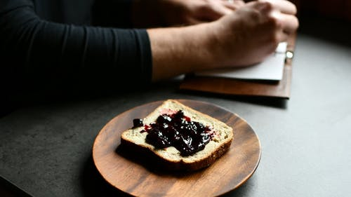 Person Writing in Notebook Eating Bread