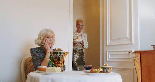 Elderly Women Bringing a Birthday Cake