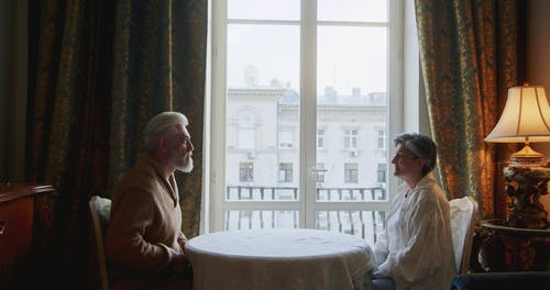 An Elderly Couple Holding Hands at the Table