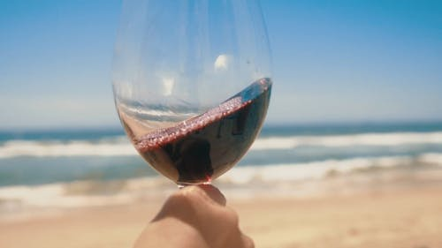 Person Drinking Wine on the Glass while on the Beach