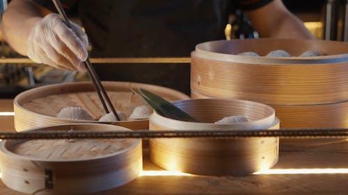 Person Putting Dumplings on a Mini Bamboo Steamer
