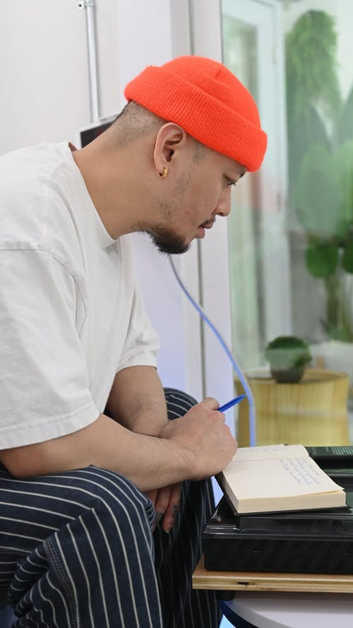 Man Writing on a Notebook