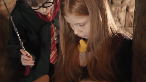 Kids in Harry Potter Costume Reading a Book