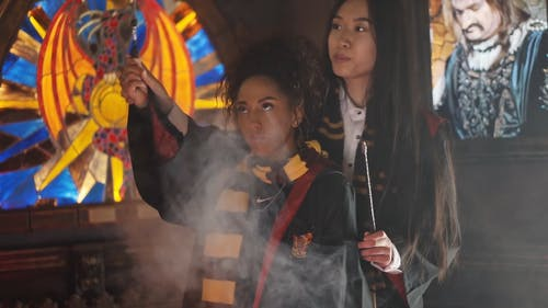 Women in Harry Potter Costumes Waving a Wand
