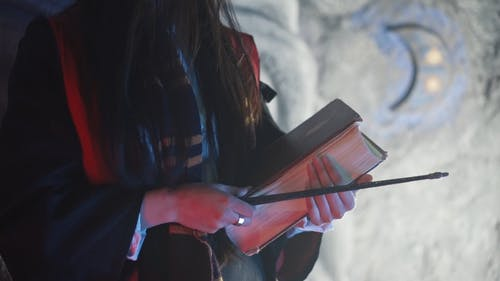 Woman Posing With Book And Wand