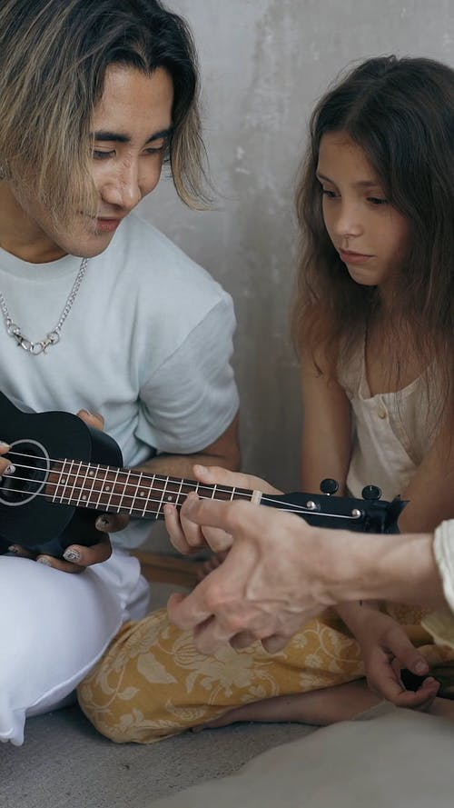 A Father Teaching Daughter Playing a Ukulele