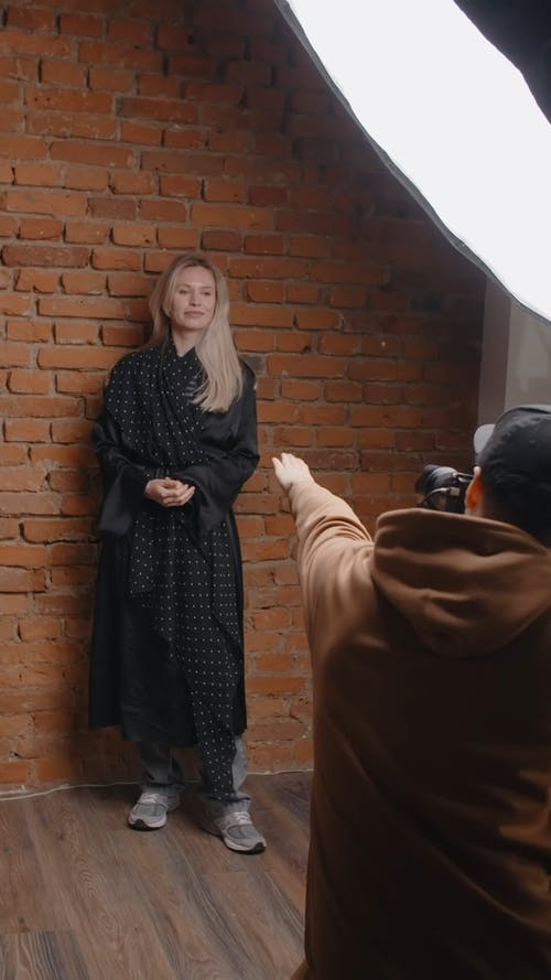 A Photographer And Blonde Woman In Black Dress Doing A Photoshoot
