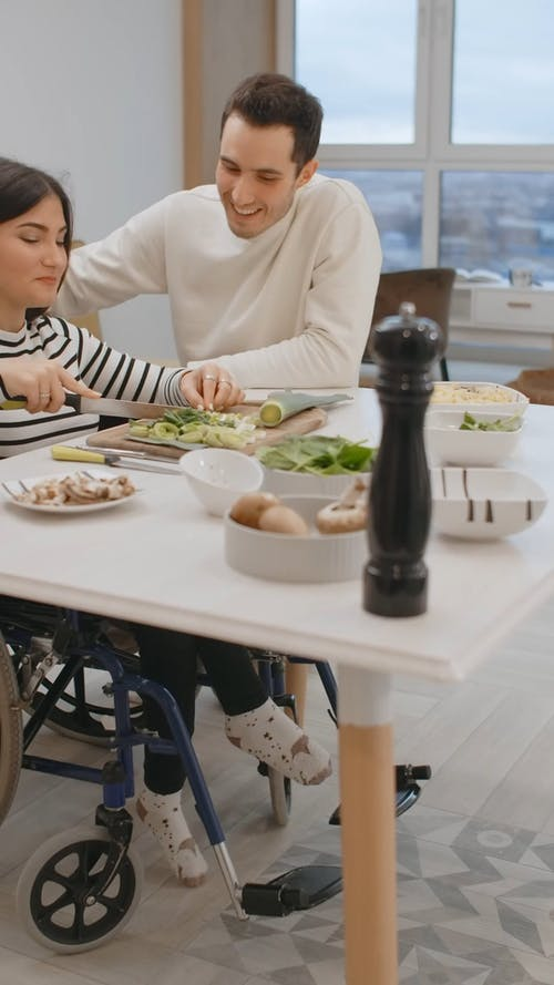 Woman Slicing the Vegetable while Talking to her Husband