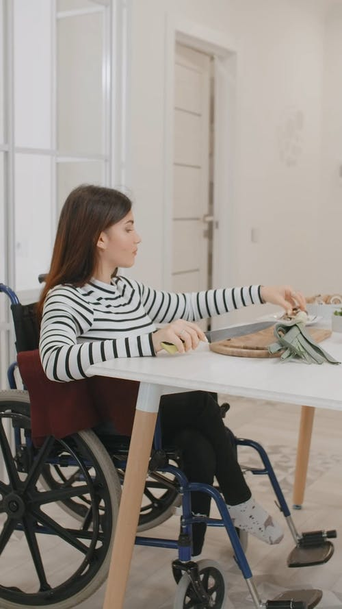 A Woman Cutting Vegetables While Sitting on a Wheelchair