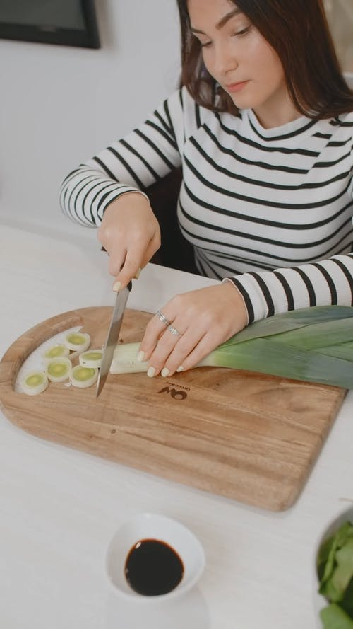 A Woman in Wheelchair is Cutting Vegetables
