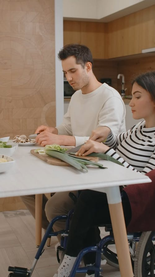 A Man and a Woman in Wheelchair are Slicing Vegetables