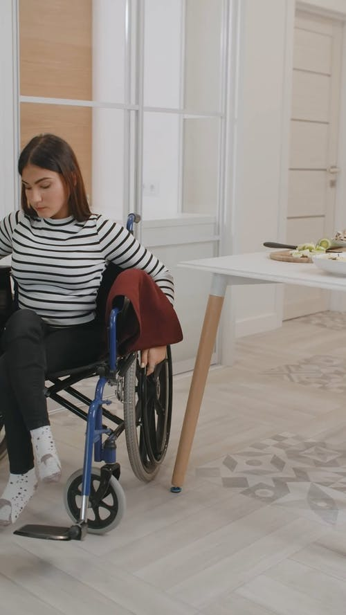 A Woman Moving Around the Kitchen in Wheelchair