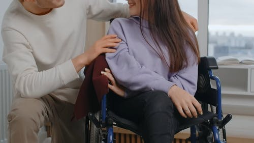 A Woman in Wheelchair is Talking and Smiling With a Man Beside Her