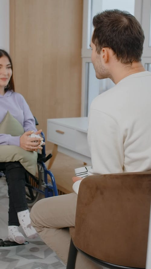 A Woman in Wheelchair is Talking and Smiling to a Man in Front of Her