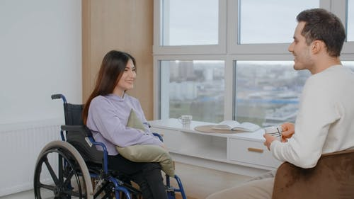 A Man and a Woman in Wheelchair are Talking