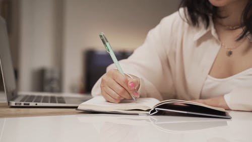 A Woman Writing on a Notebook