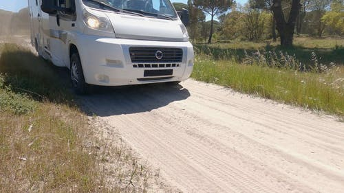 A Camper Van Driving on an Unpaved Road
