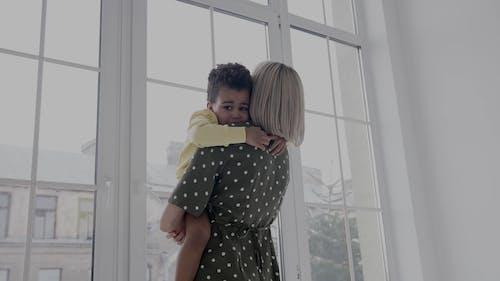 A Woman Carrying a Little Boy