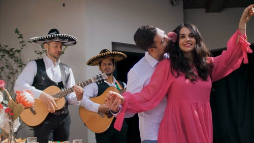 A Couple Dancing and Kissing While Men Behind are Playing Guitars