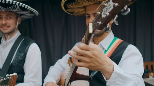 Close Up View of Men Playing Guitars