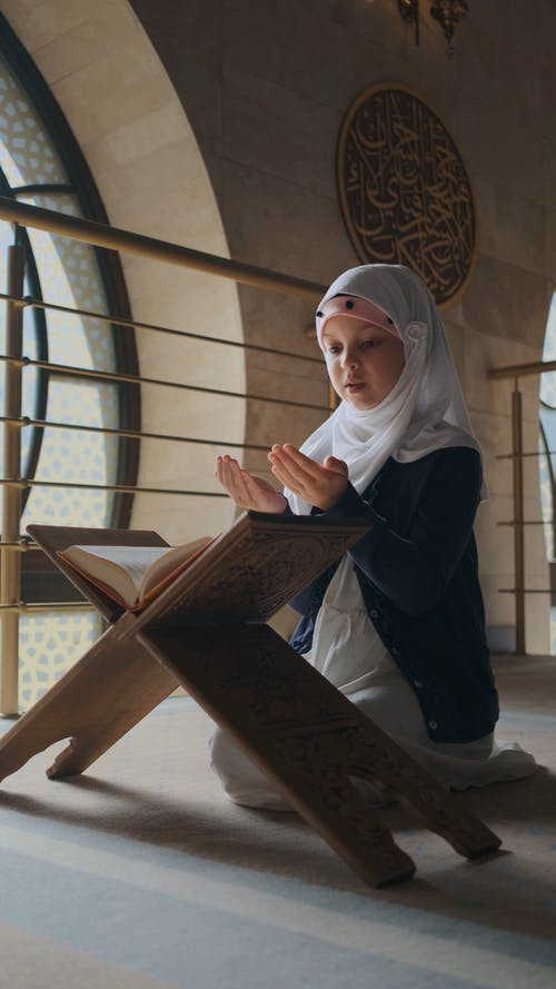 A Girl Reading and Praying the Quran