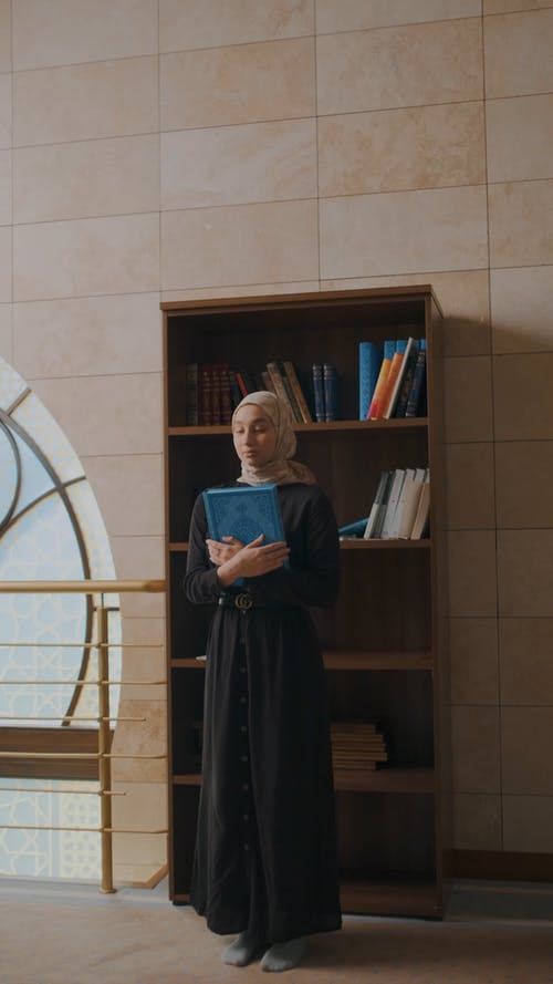 A Woman Standing by the Book Shelf Holding a Quran