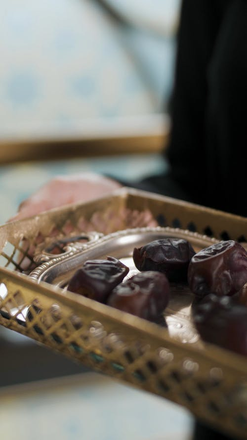 A Woman Holding a Tray with Dates and Glass of Water