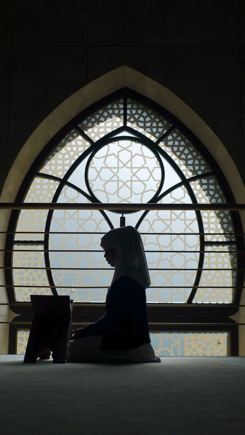 A Silhouette of a Girl Praying and Reading the Quran