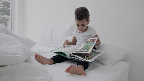 A Little Boy Holding Book while Sitting on Bed