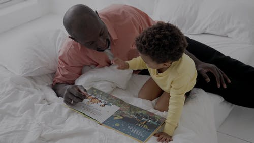 Father and Son Reading a Book on Bed