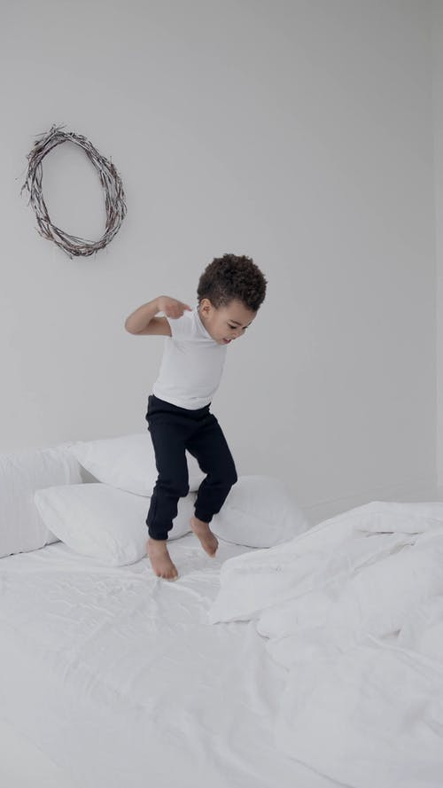 A Little Boy Jumping on the Bed