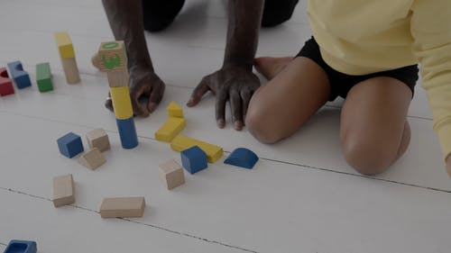 A Kid Playing With Wooden Building Blocks