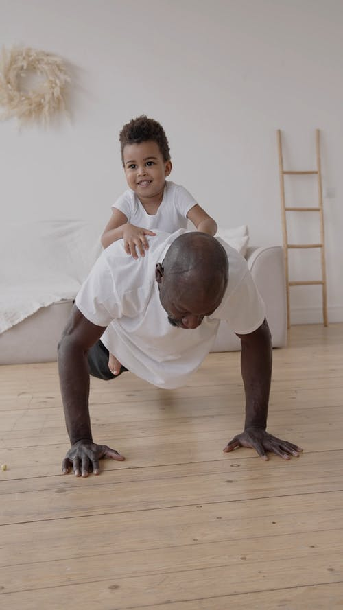 A Man Doing Push Ups with a Little Boy on his Back