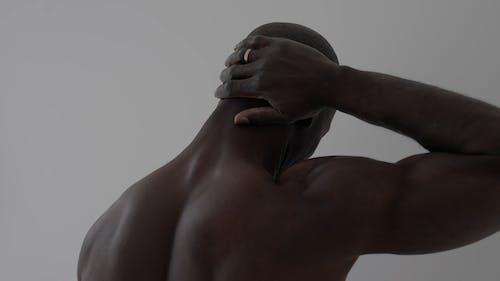 A Man Touching His Nape