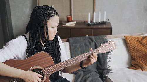 A Guitar Playing Woman at Home