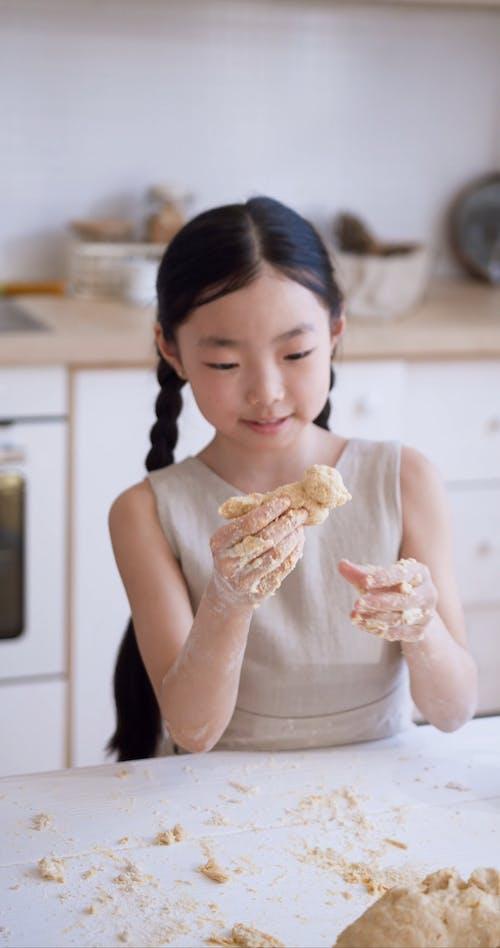 A Girl Shaping A Dough