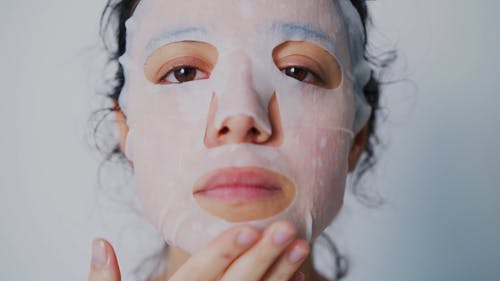 A Woman with Facial Mask Massaging Her Face