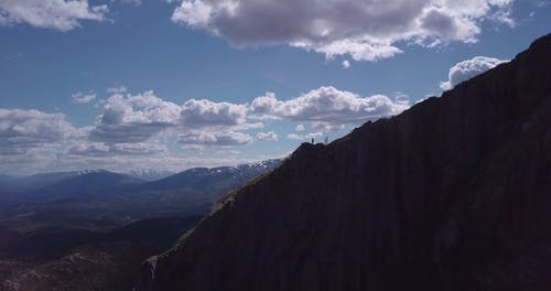A Person Standing on a Mountain Cliff