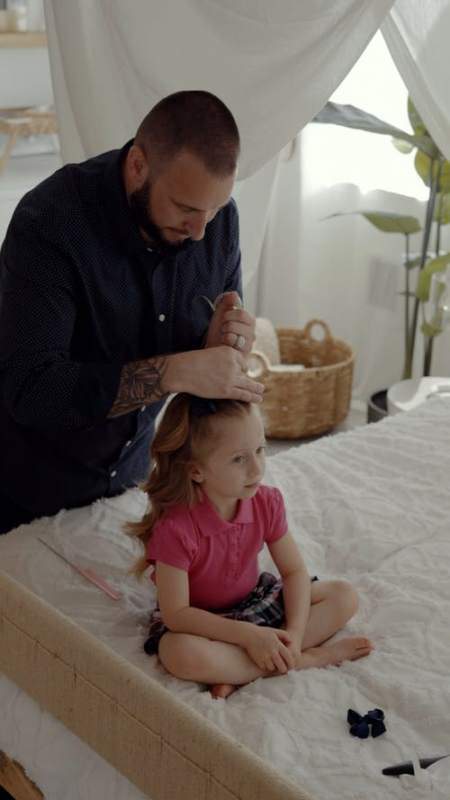 A Father Tying the Hair of Her Daughter