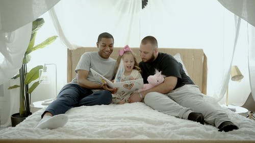 Men Sitting on Bed With Their Daughter
